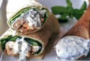 A tandoori chicken wrap with lettuce, chicken, in a flour tortilla
