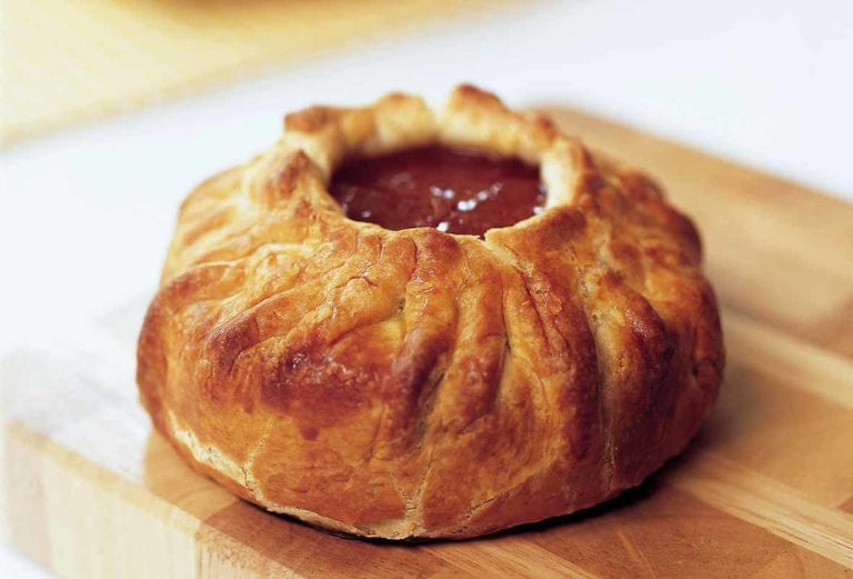 A wheel of brie cheese baked pastry, on top is a dollop of apricot preserves