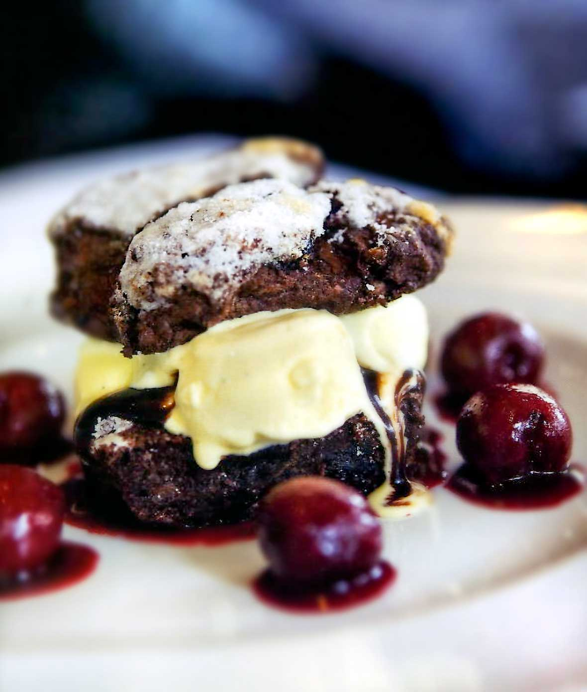 A chocolate cherry shortcake filled with vanilla ice cream and drizzled with a Cherries Jubilee sauce on a white plate