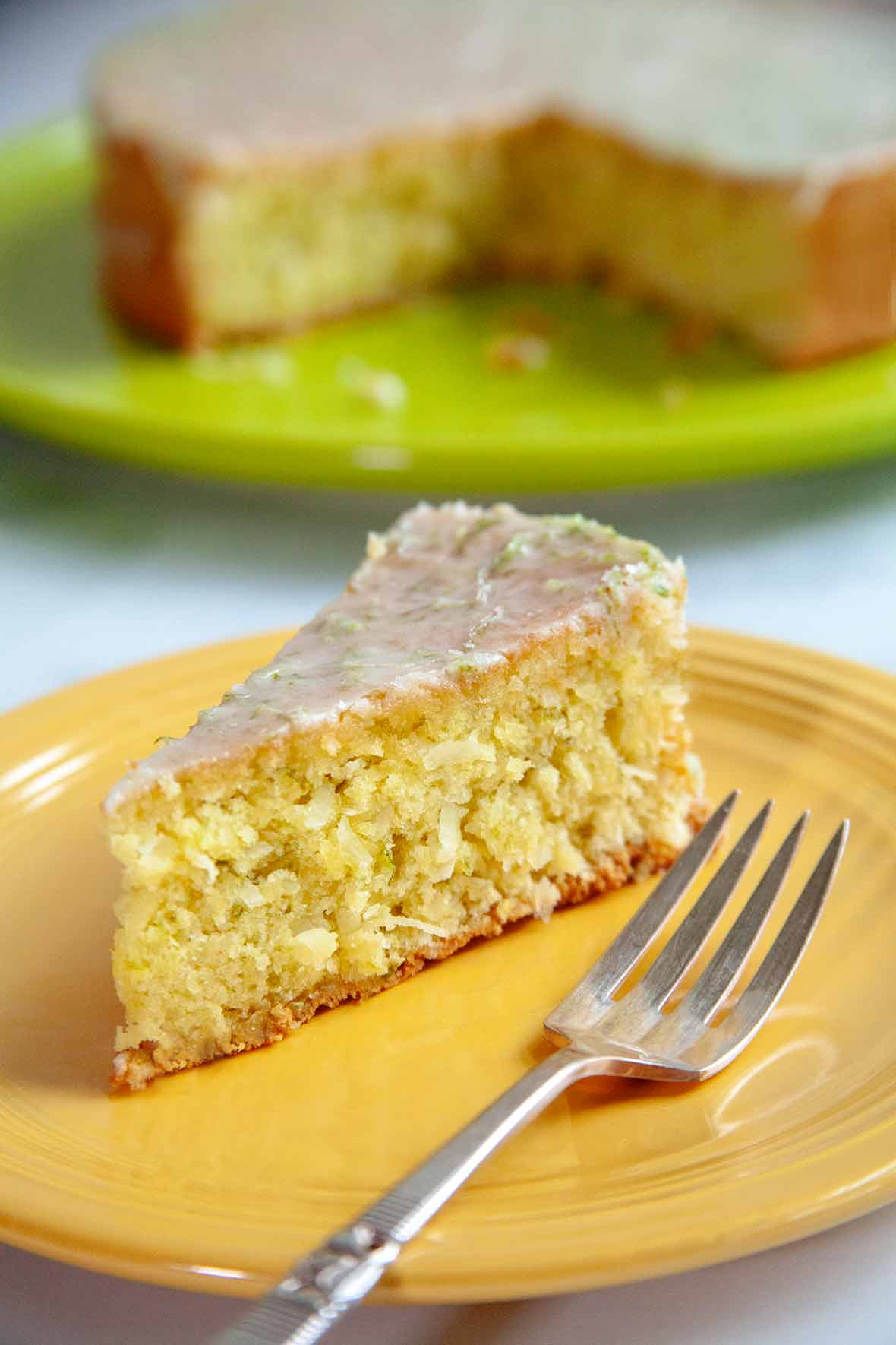 A slice of coconut lime macadamia cake on a yellow plate with a fork resting beside it