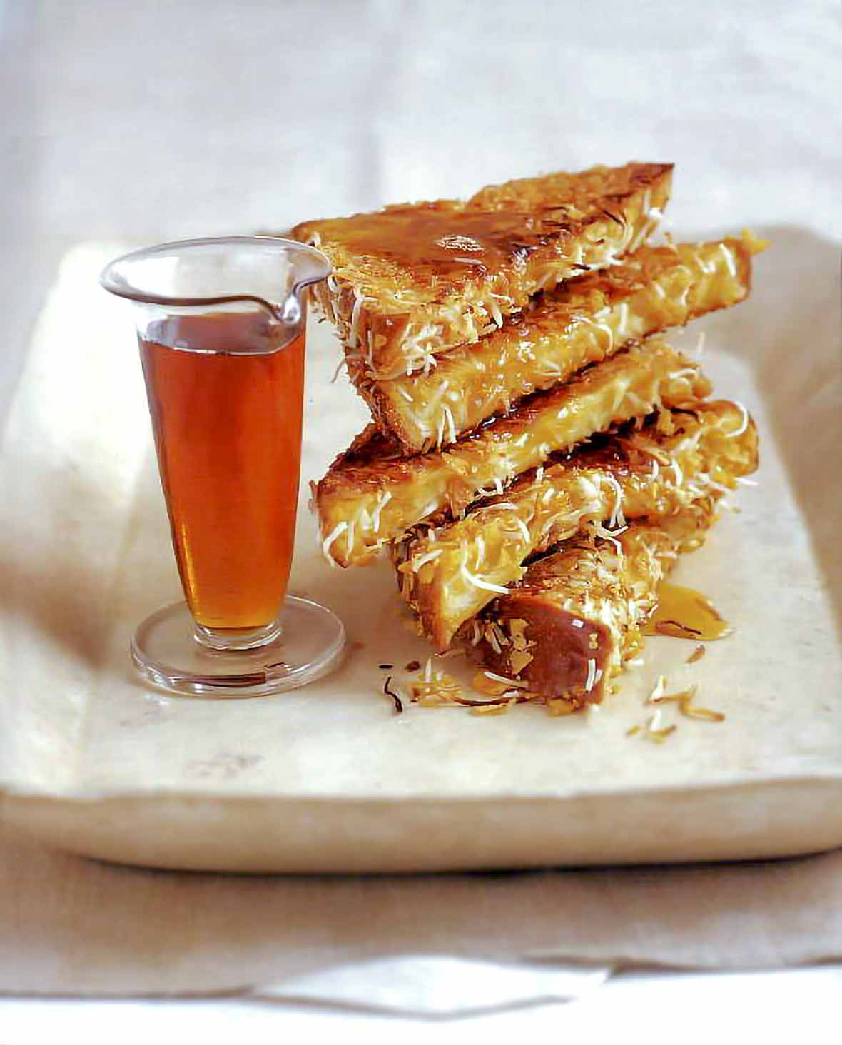 A stack of five slices of coconut french toast sprinkled with toasted coconut and dripping with maple syrup on a plate