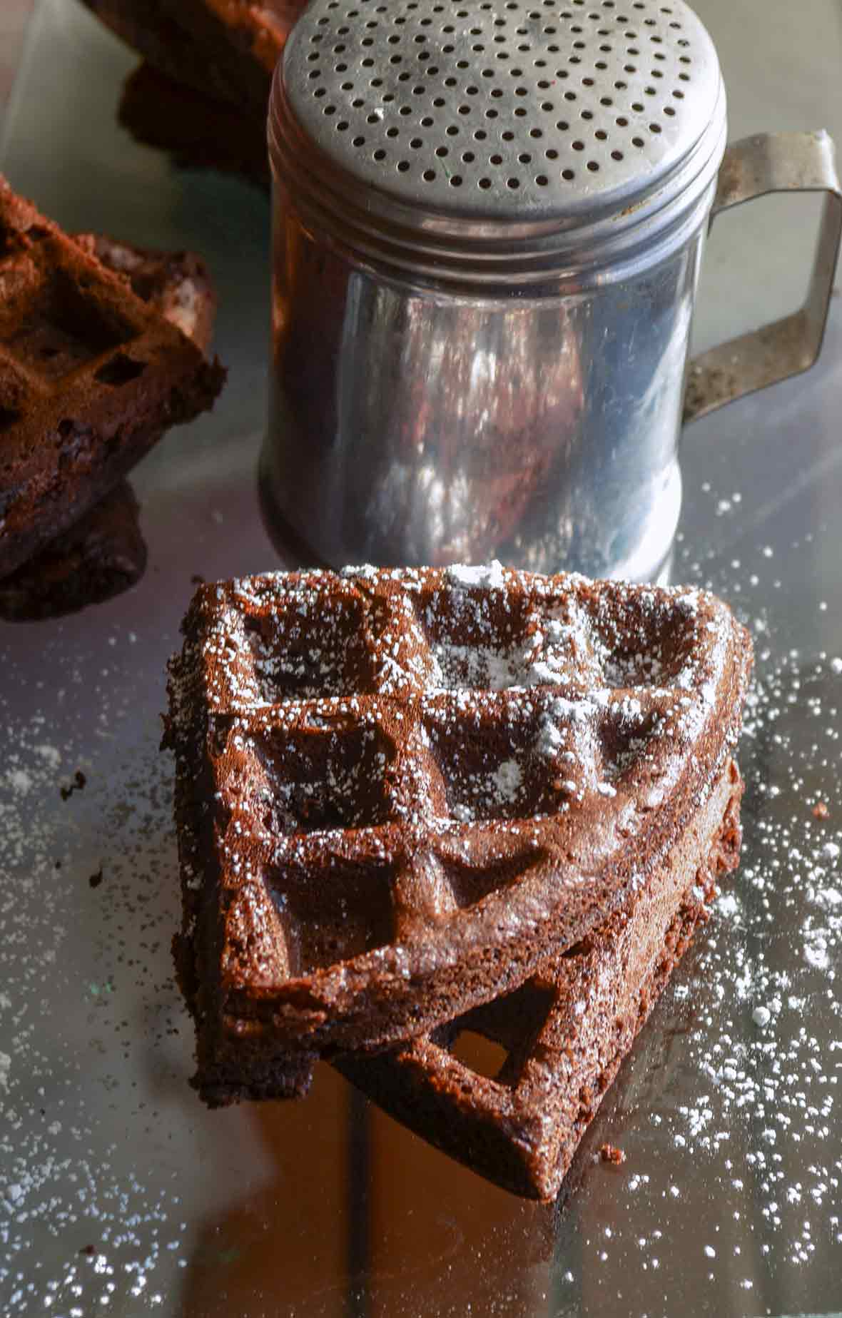 Two dark chocolate waffles on a mirrored surface sprinkled with powered sugar
