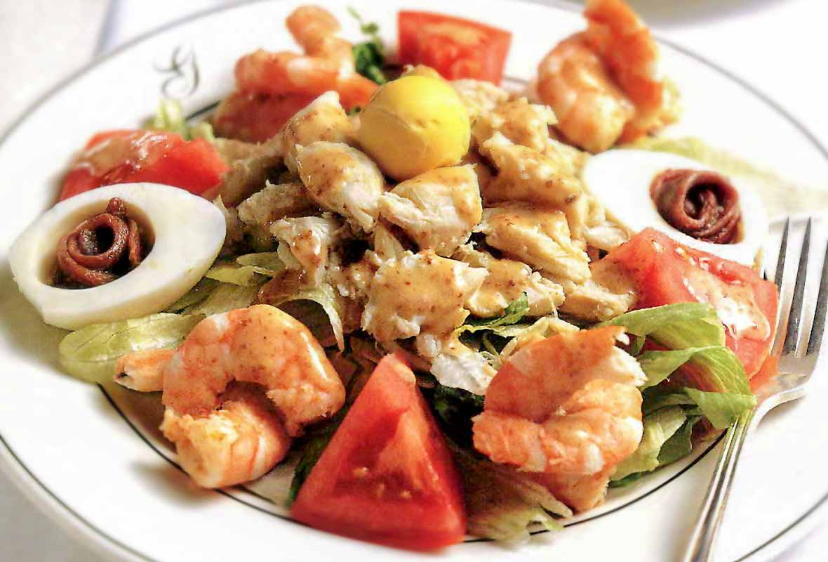 A Creole crab-shrimp salad--crab, shrimp. tomato, lettuce, boiled egg, anchovies--on a white plate