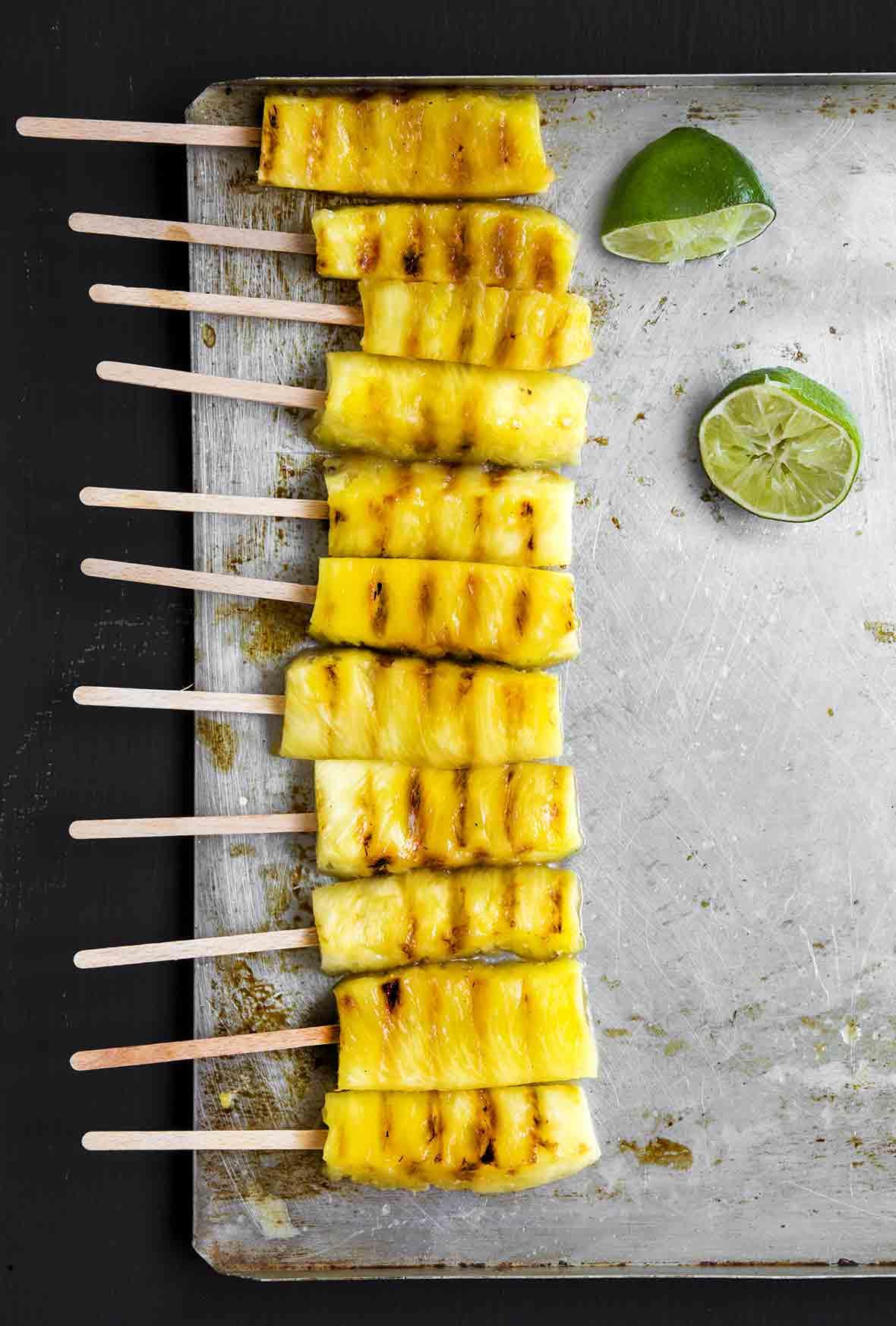Ten grilled pineapple skewers on a metal baking sheet.