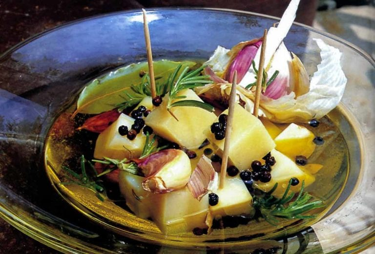 Marinated Idiazábal cheese chunks, garlic, and rosemary on a glass plate