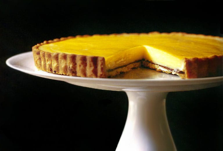 Meyer lemon tart on a white cake stand black background