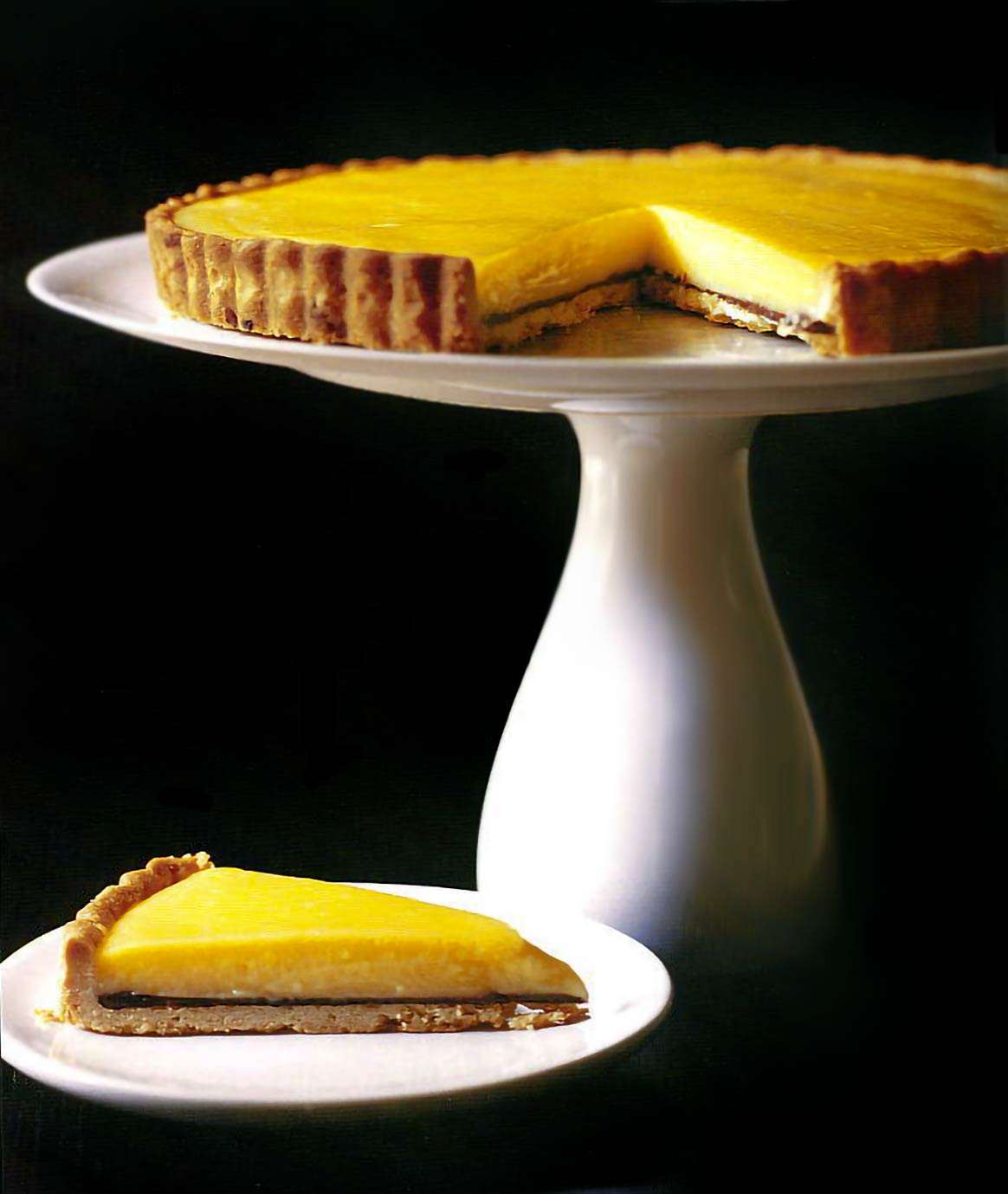 Meyer lemon tart on a white cake stand and a slice of tart on a small plate, black background