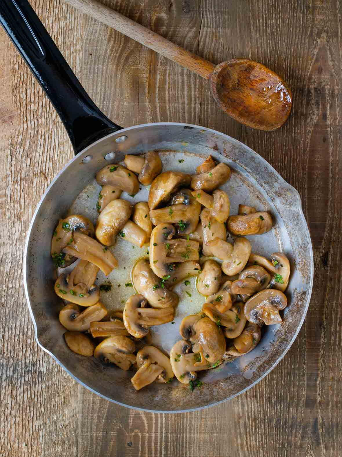 A skillet filled with mushrooms with garlic and sherry, sprinkled with parsley, and a wooden spoon resting beside it.