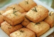Platter of square rosemary corn scones with sprigs of rosemary sticking out of their tops