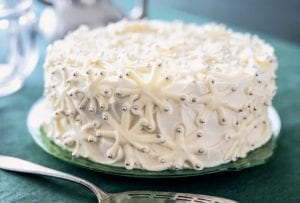 A snowflake cake decorated with white chocolate snowflakes and silver dragees on a green plate.