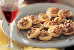 A grey plate filled with stilton pinwheels with walnuts and honey on a yellow cloth.