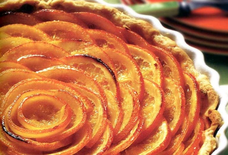 A Valencian orange tart with slices of oranges in a circular pattern in a pastry crust