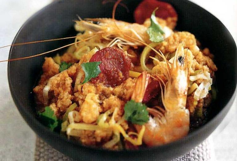 Black bowl of Portuguese bread soup--called acorda--with shrimp, sausage, tomatoes, garlic, cilantro