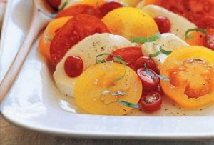 A white serving platter filled with Caprese salad made with sliced tomatoes, sliced mozzarella, and fresh basil with a serving spoon resting inside.