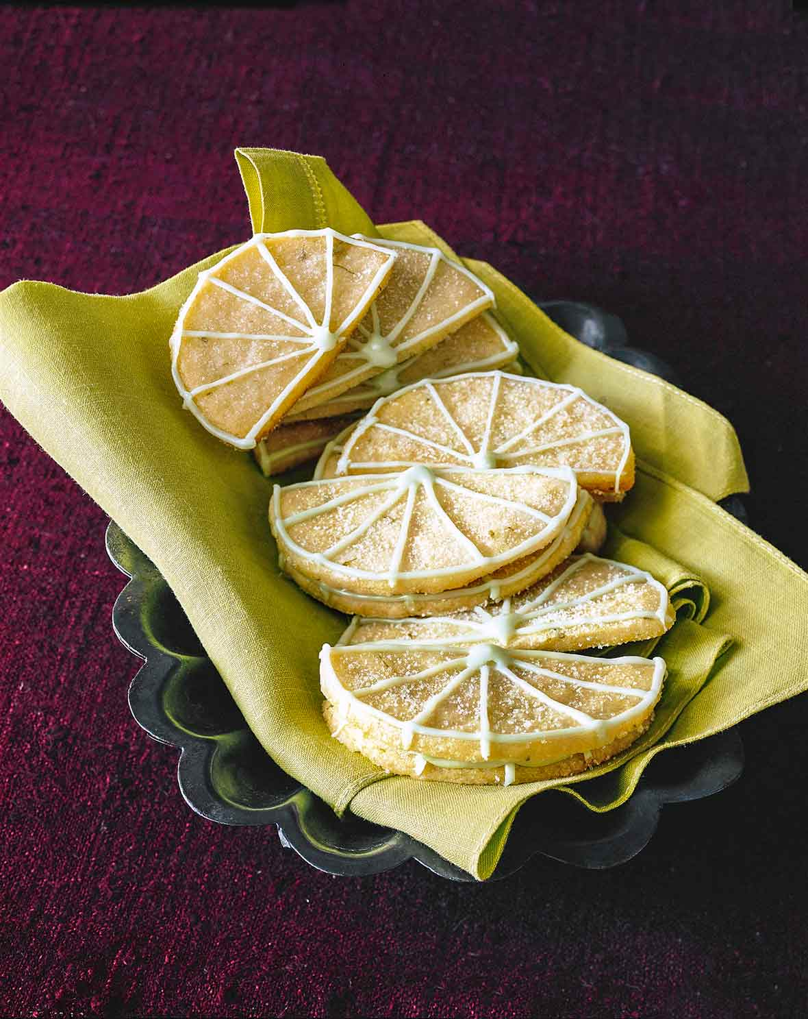 12 Key lime sugar cookies in the shape of lime wedges with lime icing