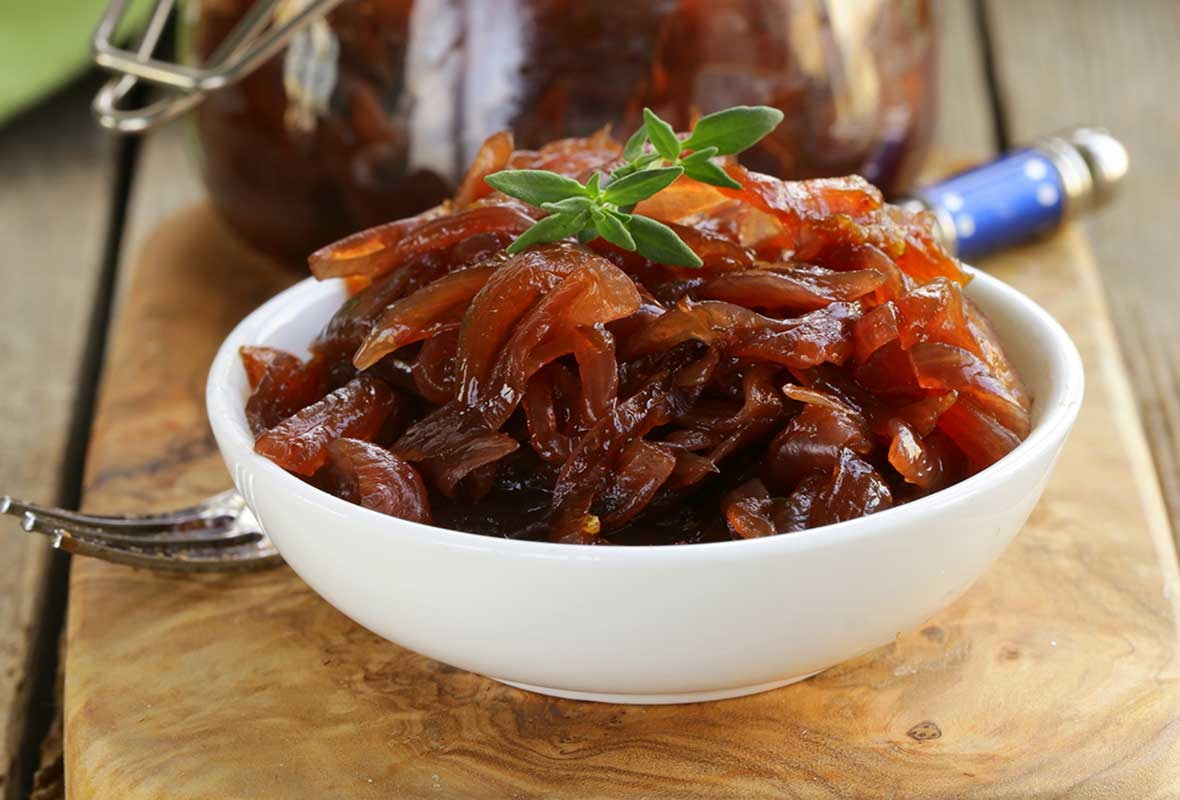 White bowl of onion marmalade--sliced, cooked onions--in front of a mason jar, on a wood plank