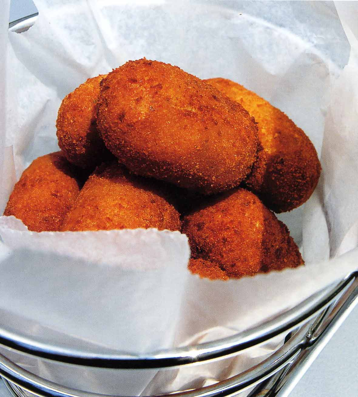 Batch of deep-fried oval Spanish serrano ham and chicken fritters in a metal basket