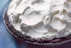 A chocolate cream pie, with a chocolate crumb crust and topped with whipped cream, on a blue background