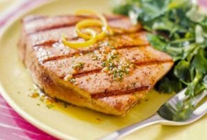 A grilled tuna steaks with spiced vinaigrette with lemon zest on top, a salad on the side