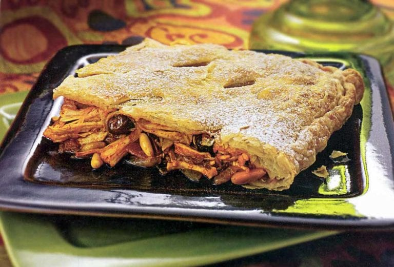 A square slice of Moorish chicken and nut pie--with chicken pine nuts, almonds, raisins spilling form a puff pastry top and bottom crust