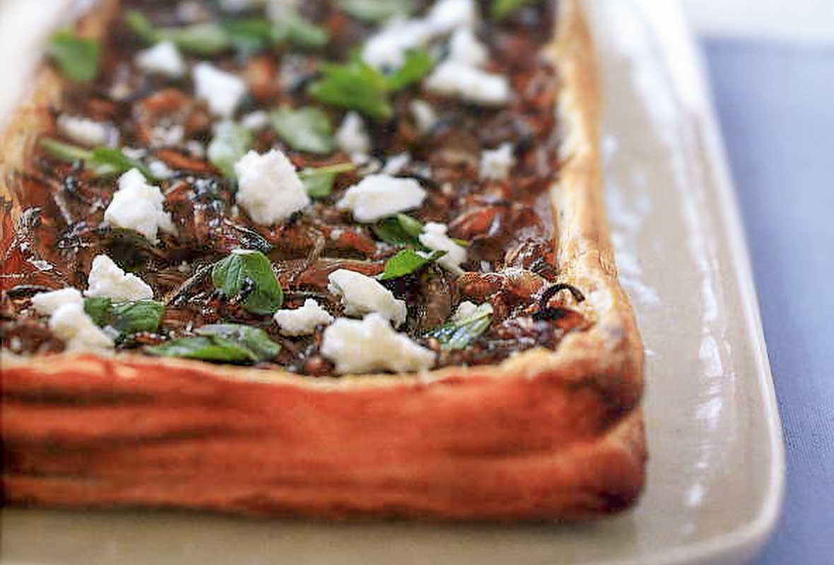 An onion and feta cheese tart with a puff pastry crust filled with caramelized onions, crumbled feta cheese, and basil