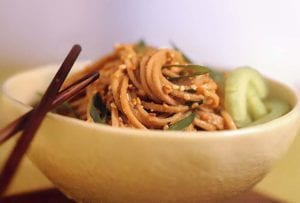 A bowl of sesame-peanut noodles coated in peanut sauce, topped with sesame seeds, chopsticks on the side