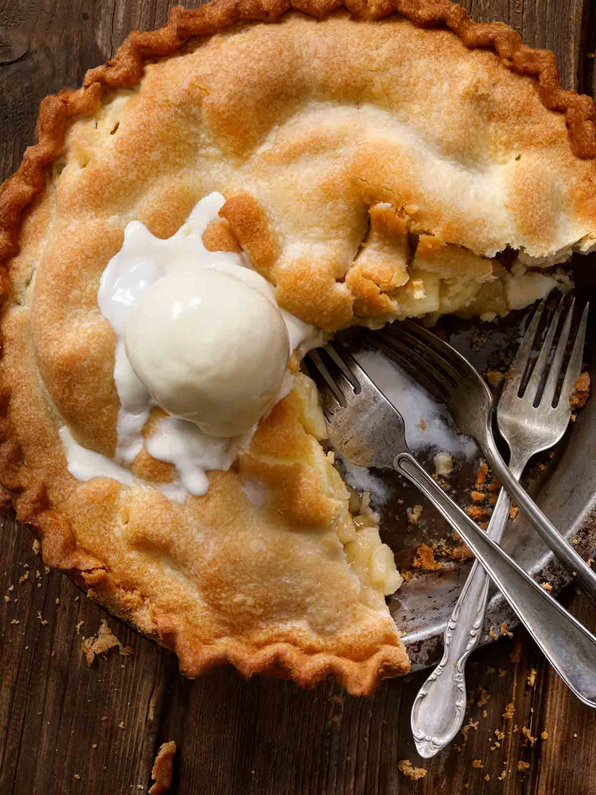 A classic apple pie with one-quarter missing, topped with a scoop of ice cream, and three forks in the empty pie spot.