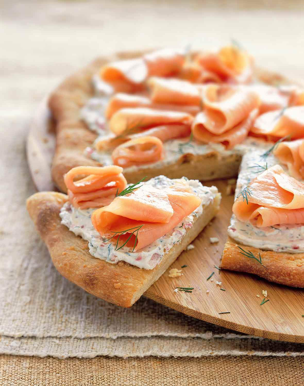 A smoked salmon pizza with cream cheese, red onion, and dill with one wedge cut out.