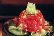 Wooden pedestal topped with tuna tartare with cucumber salad and avocado