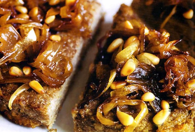 Lamb kibbeh cut into wedges topped with caramelized onions and toasted pine nuts