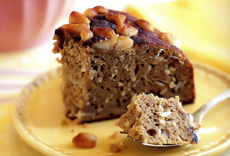 A slice of banana and macadamia nut coffee cake on a yellow plate with a fork holding a bite of it.