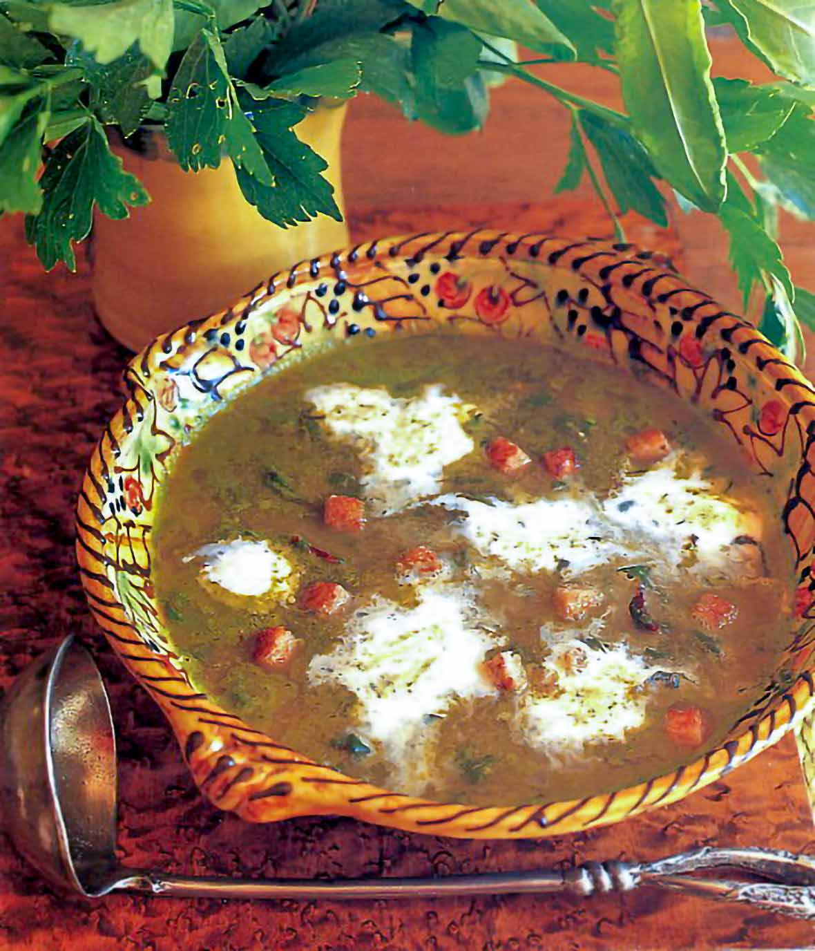 A decorated clay bowl filled with spring soup of spinach, lettuce, and sorrel, dotted with cream, bacon, and bread cubes