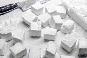 Cubes of homemade marshmallows on a white surface with a chef's knife lying beside.