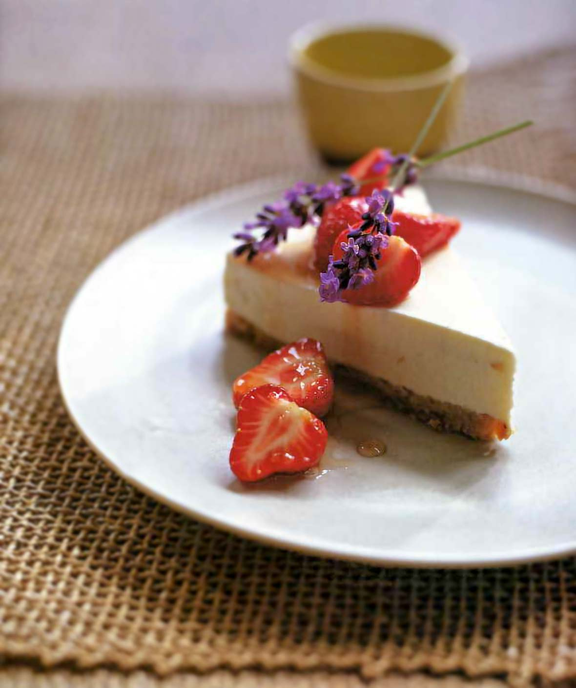 A white plate with a slice of lavender yogurt cheesecake topped with lime-infused strawberries and a sprig of lavender