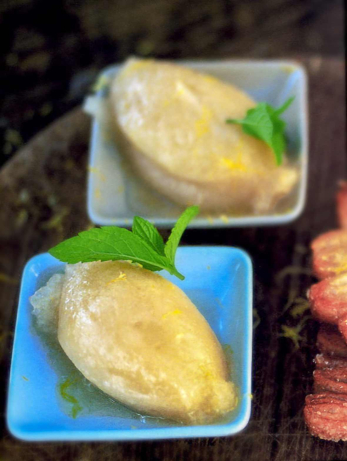 Two plates with a scoop each of pear sorbet and a mint leaf