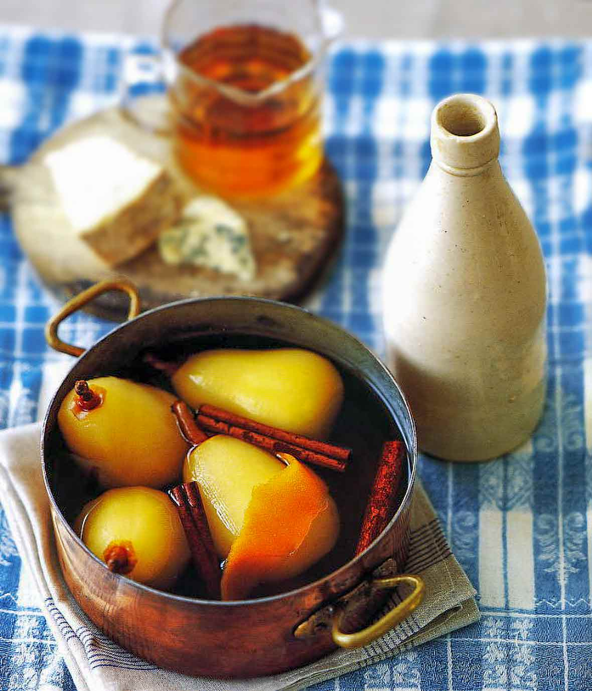 Copper pot filled with four pears poached in mead and cinnamon, a bottle, and platter of cheese