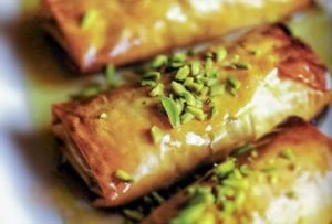 Four phyllo pastries stuffed with nuts, honey, and orange blossom water, and topped with pistachios and more honey