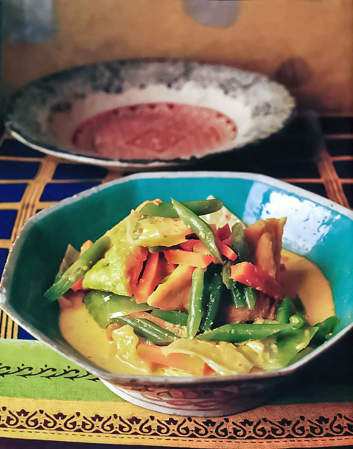 An octagonal bowl filled with tofu and vegetables in coconut milk on a colorful cloth with a large bowl in the background.