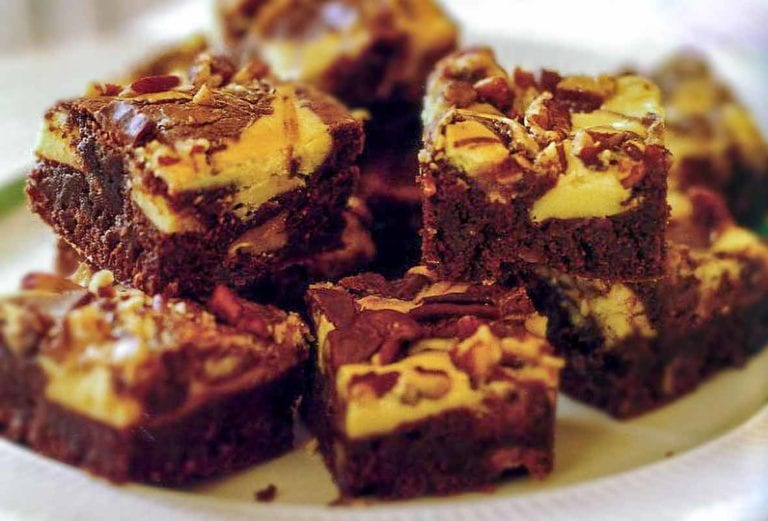 Plate of cream cheese swirl brownies with layers of chocolate, cheese cake, Heath bar, and pecans
