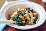 Bowl of cvatelli with turkey sausage, tomato, and broccoli rabe on a table, with a spoon
