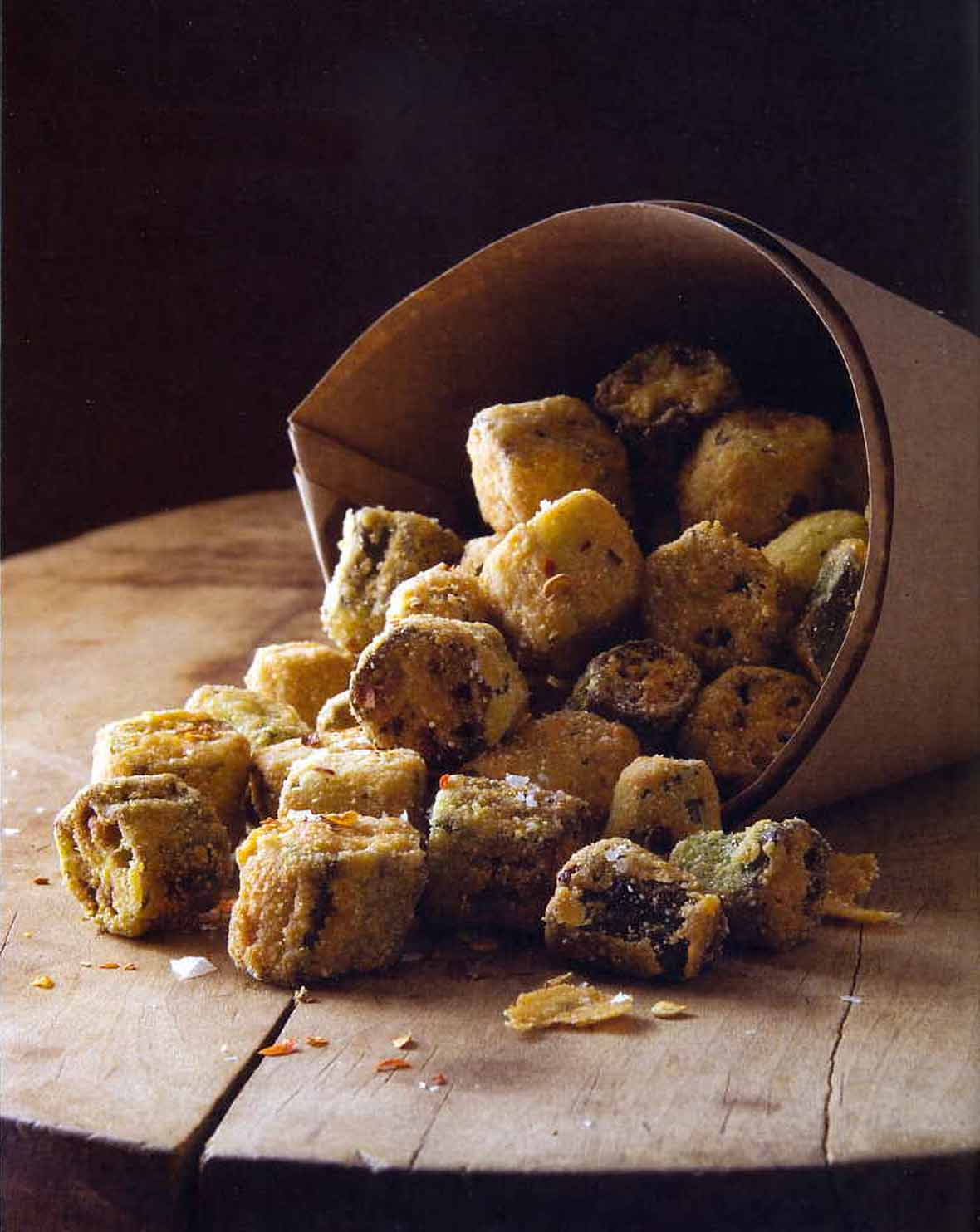 Paper cone with crispy fried okra bites spilling out on top a wooden board