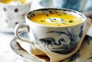 A blue and white tea cup filled with yellow pumpkin-cider soup