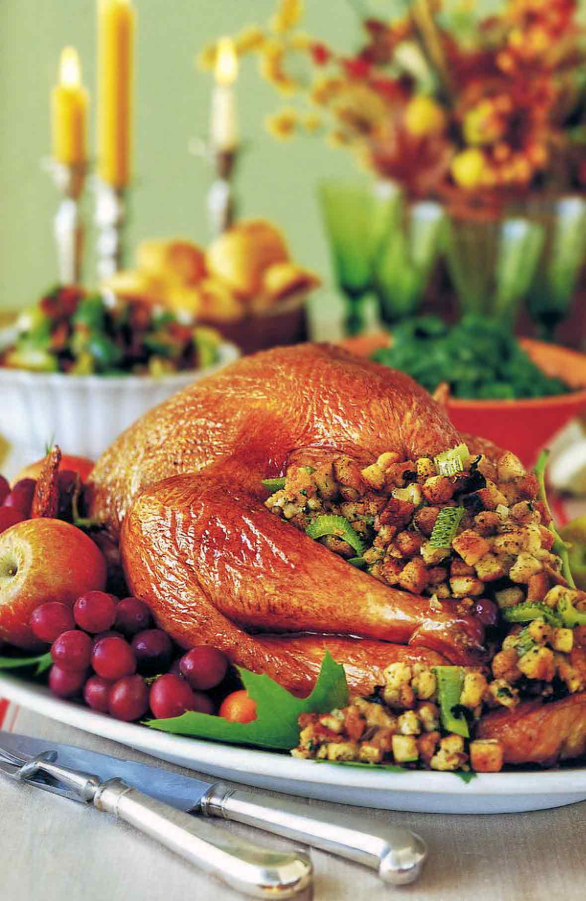 Thanksgiving table with a Roast turkey with stuffing and vegetables on a platter