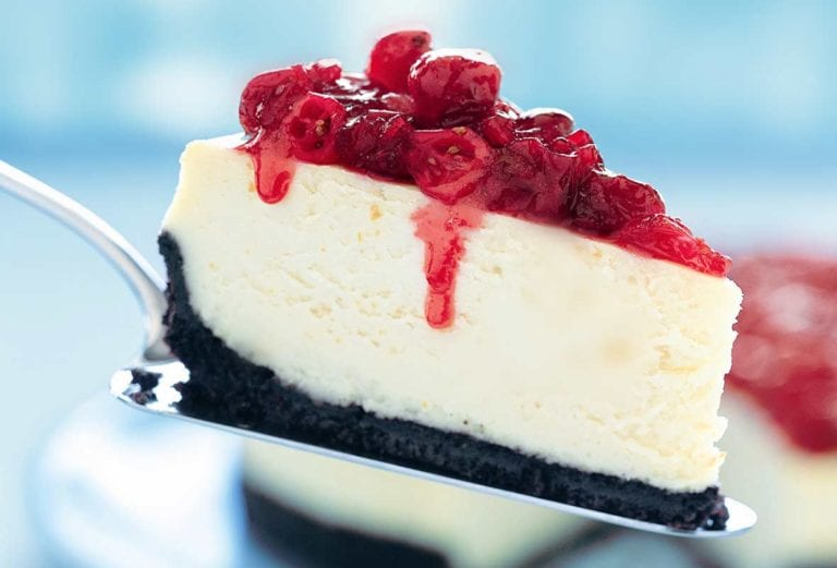 A slice of cheesecake topped with cranberries on a silver cake lifter