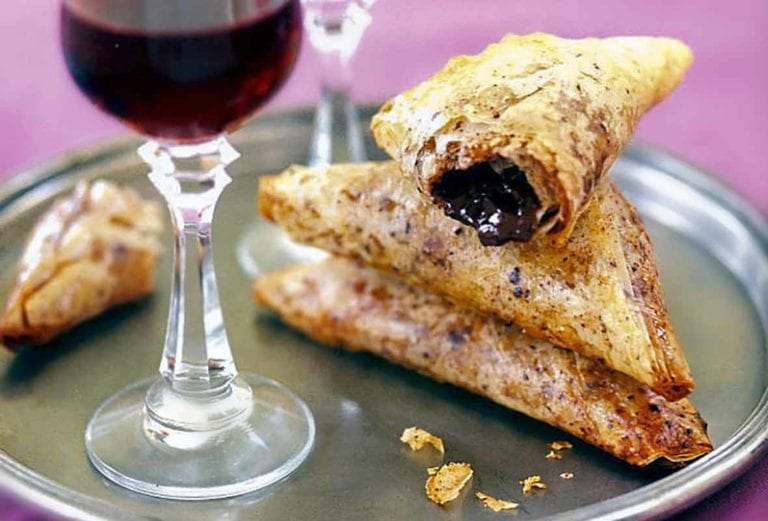Crispy chocolate-filled pastry triangles and two glasses of dessert wine on a silver tray