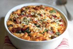 A white bowl of savory bread pudding with peppers, bacon, and spinach on top of a folded napkin