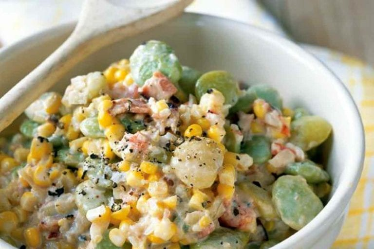 A white bowl filled with Delaware creamed succotash with a wooden spoon resting on top.