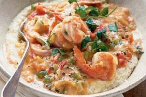 A white bowl filled with Tennessee shrimp and grits, topped with a sprig of parsley.