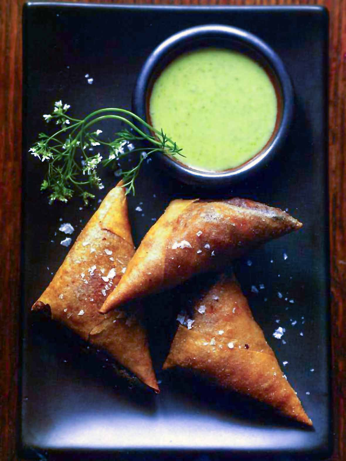 Three chicken samosas on a black plate with cilantro-yogurt dip
