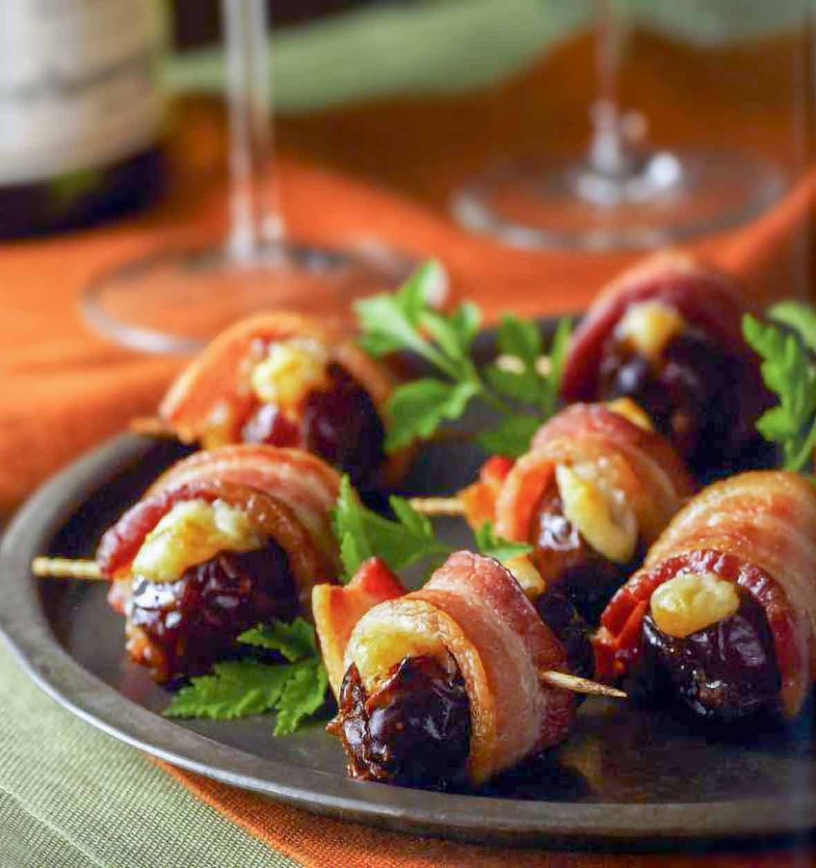 Plate of crispy bacon-wrapped stuffed dates held by toothpicks, parsley garnish